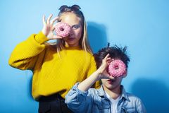 Happy family brother and sister eating donuts on blue background, lifestyle people concept, boy and girl eating. Unhealthy closeup royalty free stock image
