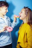 Happy family brother and sister eating donuts on blue background, lifestyle people concept, boy and girl eating. Unhealthy closeup royalty free stock photo