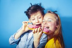 Happy family brother and sister eating donuts on blue background, lifestyle people concept, boy and girl eating. Unhealthy closeup stock photography