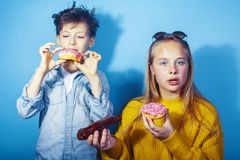 Happy family brother and sister eating donuts on blue background, lifestyle people concept, boy and girl eating stock photo