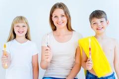 Family brushing teeth. Happy family brushing teeth in a bathroom Royalty Free Stock Photography