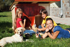 Happy family building a doghouse together. Happy family building a doghouse for their little labrador puppy - painting Stock Image