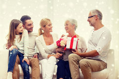 Happy family with bunch and gift box at home. Family, happiness, generation, holidays and people concept - happy family with bunch of flowers and gift box stock images