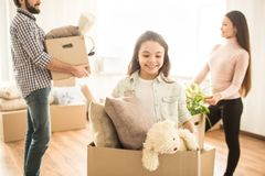 Happy family is busy. Everybody has some work to do. Father and his daughter are holding boxes with toys and different. Stuff while young women has a plant in royalty free stock photos