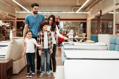 Happy family buys new orthopedic mattress in furniture store. Blissful family choosing mattresses in store. royalty free stock photos
