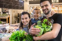 Happy family buys vegetables. Cheerful family of three choosing tomatoes in vegetable department of supermarket or market royalty free stock photo