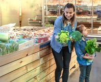 Happy family buys vegetables. Cheerful family of three choosing tomatoes in vegetable department of supermarket or market stock photo