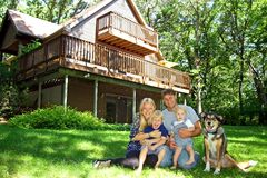 Happy Family at Cabin in the Woods. A happy, smiling family of four people; mother, father, baby, and young child, and their dog, are sitting in the grass in royalty free stock photography