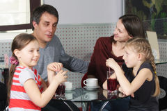 Happy family in cafe. Happy family sitting in cafe at glass table and chatting Royalty Free Stock Photography
