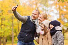 Happy family with camera in autumn park Royalty Free Stock Photos