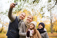 Happy family with camera in autumn park Stock Image