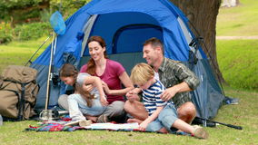 Happy family on a camping trip in front of their tent stock video footage