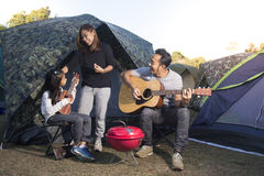 Happy family on a camping trip. Parents and daughters are singing guitar royalty free stock photography