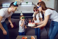 A happy family with a candle cake celebrates a birthday party stock images