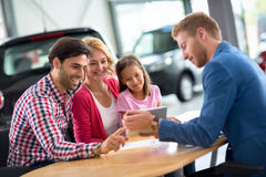 Happy family in car dealership choosing their new car Stock Images