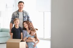 Happy family with cardboard box indoors. Moving into new house royalty free stock photos