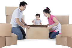 Happy family with cardboard on studio. Image of happy family unpacking cardboard while kneeling in the studio, isolated on white background Royalty Free Stock Image