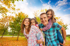 Happy family carry little girls in the autumn park Royalty Free Stock Photo