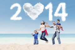 Happy family celebrate new year 2014 at beach. Happy family having fun in the beach with heart shaped cloud of new year 2014 Stock Image
