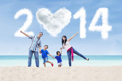 Happy family celebrate new year 2014 in the beach. Happy family having fun in the beach with heart shaped cloud of new year 2014 Stock Photography