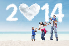 Happy family celebrate new year at beach. Happy family having fun in the beach with heart shaped cloud of new year 2014 Stock Photos