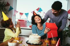 Family celebrating a birthday together at home. Happy family celebrating a birthday together at home stock images
