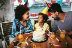 Family celebrating a birthday together at home. Happy family celebrating a birthday together at home stock photo
