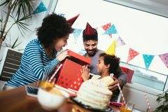 Family celebrating a birthday together at home. Happy family celebrating a birthday together at home royalty free stock photo