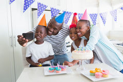 Happy family celebrating a birthday together and taking a selfie. At home in the kitchen royalty free stock photo
