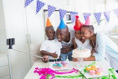 Happy family celebrating a birthday together and taking a selfie. At home in the kitchen stock photos