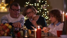 Happy family celebrating Christmas by candlelight against the background of New Year`s lights. Grandpa puts salad in his. Grandson`s plate. Vegetarian dinner stock video