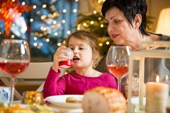 Happy family celebrating Christmas. Happy family celebrating holiday together, sitting around decorated round table, Grandma and kid . Living room with Christmas Royalty Free Stock Image