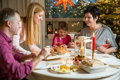 Happy family celebrating Christmas. Happy family celebrating holiday together, sitting around decorated round table. Mother serving dinner. Living room with Royalty Free Stock Photos