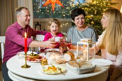 Happy family celebrating Christmas. Happy family celebrating holiday together, sitting around decorated round table, Rising glasses. Living room with Christmas Stock Photo