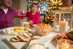 Happy family celebrating Christmas. Happy family celebrating holiday together, sitting around decorated round table, food close-up. Living room with Christmas Royalty Free Stock Photos