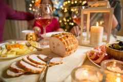 Happy family celebrating Christmas. Happy family celebrating holiday together, sitting around decorated round table, food close-up. Living room with Christmas Stock Image