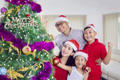 Happy family is celebrating Christmas at home. With a Christmas tree while wearing a Santa hat Royalty Free Stock Photography