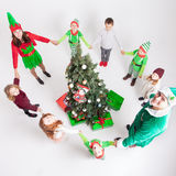 Happy family celebrating Christmas near Cristmas tree. Happy family celebrating  near Cristmas tree. Mother and children dressed in elf costumes and father in Royalty Free Stock Image
