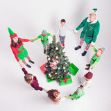 Happy family celebrating Christmas near Cristmas tree. Mother and children dressed in elf costumes and father in Santa helper. A round dance, children's party Royalty Free Stock Image