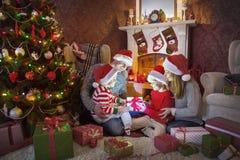 Happy family celebrating Christmas. Near the fireplace under the Christmas tree royalty free stock photo