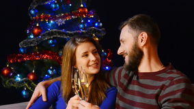 Happy family celebrating Christmas or New Year. Young couple family celebrating Christmas or New Year with glasses of champagne talking and making wishes with stock video footage
