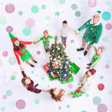 Happy family celebrating Christmas a round Cristmas tree. Royalty Free Stock Images