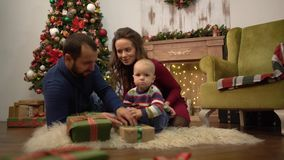 Happy family celebrating Christmas together Mother, father and little baby sitting on the floor in the room with stock video