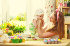 Happy family celebrating easter mother and baby with bunny ears Stock Photo