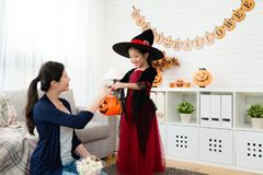 Young mom give kids with candy. Happy family celebrating Halloween, Young beautiful mom treats give kids with candy. Funny kids in carnival costumes Stock Images
