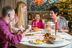 Happy family celebrating Christmas. Happy family celebrating holiday together, sitting around decorated round table. Mother serving dinner. Living room with Stock Photo