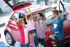 Happy family celebrating just bought a new car. Happy and excited family celebrating just bought a new car from dealership Royalty Free Stock Photography