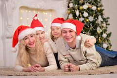 Happy family celebrating New Year Christmas. The happy family smile, lie on the floor, celebrating New Year Christmas Stock Image