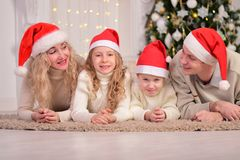 Happy family celebrating New Year Christmas. The happy family smile, lie on the floor, celebrating New Year Christmas Stock Images