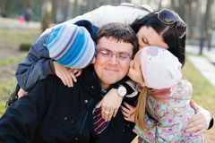 Happy family of 4 celebrating: Parents with two children having fun hugging & kissing father who is happy smile, closeup portrait. Closeup portrait of happy Royalty Free Stock Image
